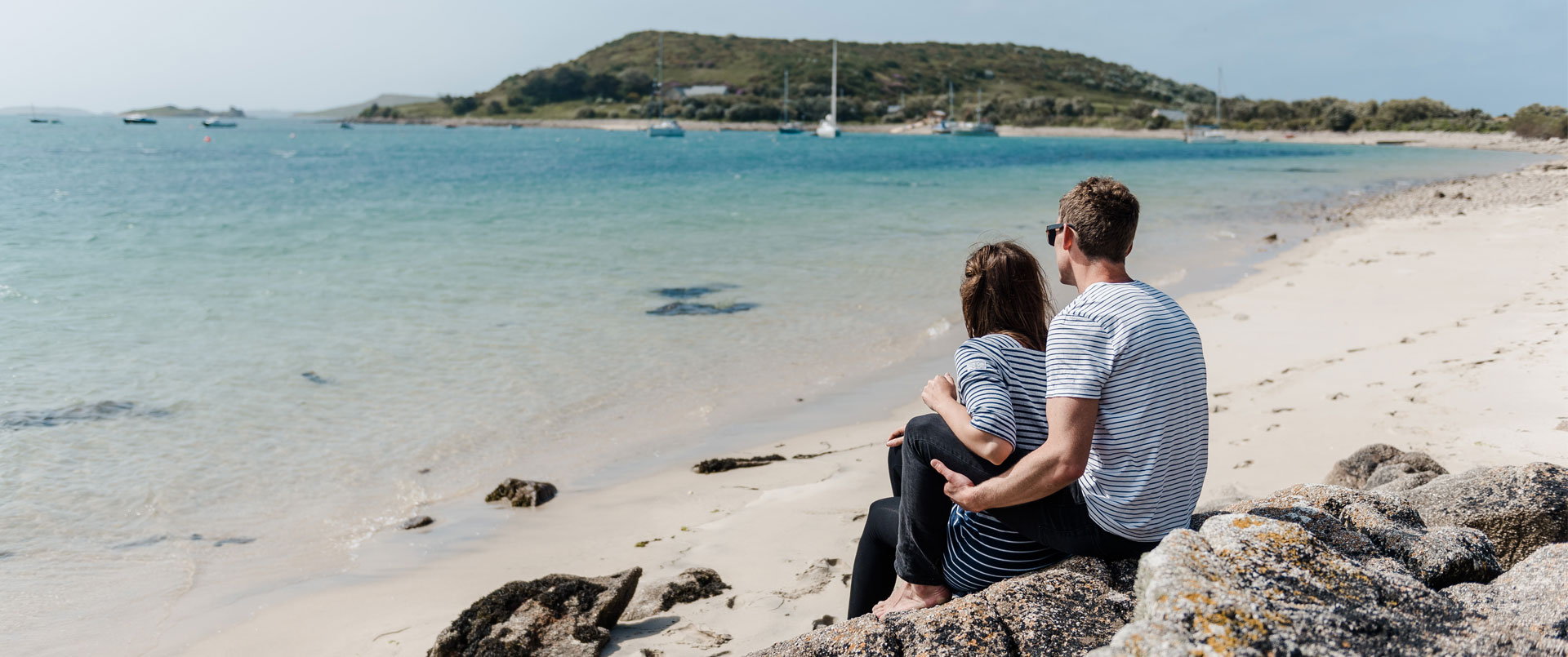 Couple looking out to sea from a beach on Bryher, Isles of Scilly